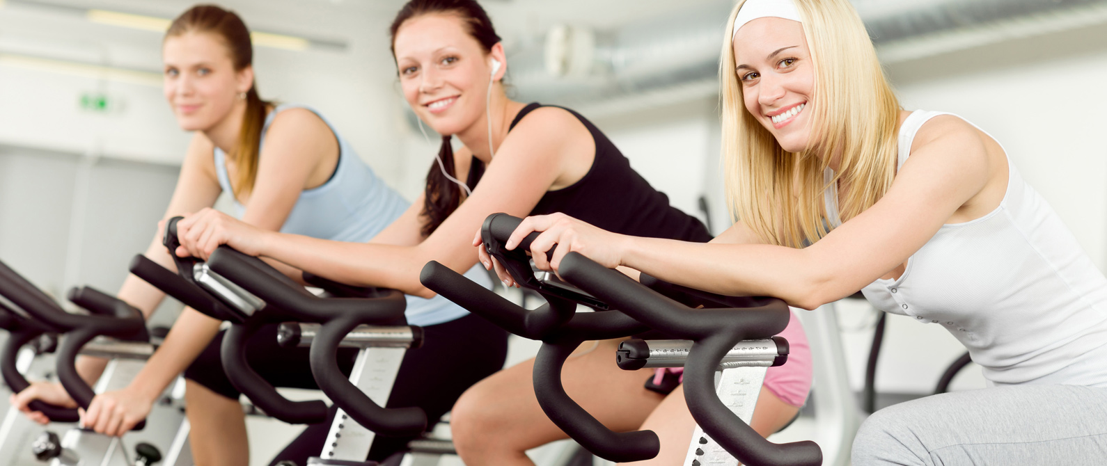 Beautiful young ladies sitting on gym cycle and smiling at camera