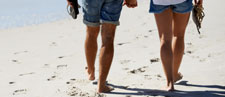 Couple walking on beach barefoot