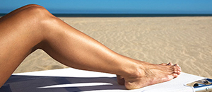 Image focusing on women legs relaxing on the beach